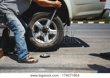 A man changing the tire at the side of the road
