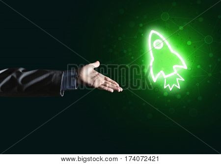Rocket glowing icon and businessman hand on dark background