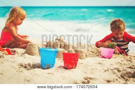 little boy and girl building sandcastle at tropical beach