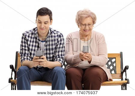 Young man and an elderly woman sitting on a bench and looking at their phones isolated on white background