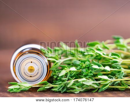 thyme essential oil and dark glass bottle with pipette and fresh thyme on dark brown wooden background with copy space