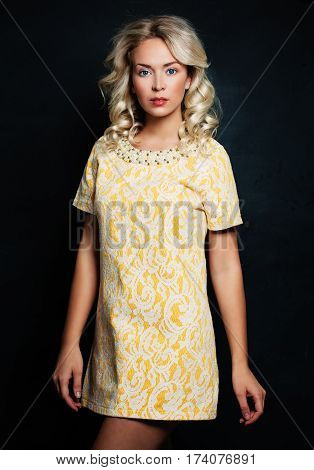 Pretty Woman with Blonde Hair. Blonde Curly Hairstyle wearing Yellow Dress