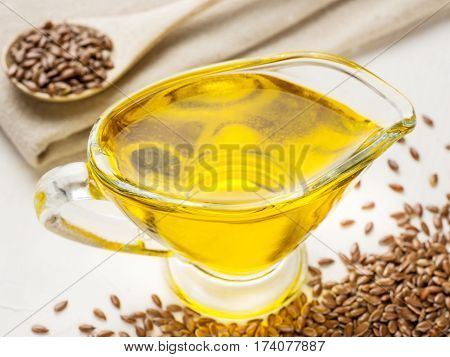 Brown flax seeds and flaxseed oil in glass jug on trendy textured white concrete background. Flax oil is rich in omega-3 fatty acid.