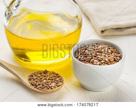 Brown flax seeds in spoon and flaxseed oil in glass bottle on trendy textured white concrete background. Flax oil is rich in omega-3 fatty acid.