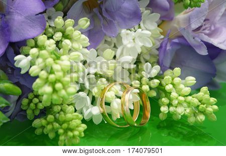 Two wedding rings and a wedding bouquet of white lilac and purple freesias.