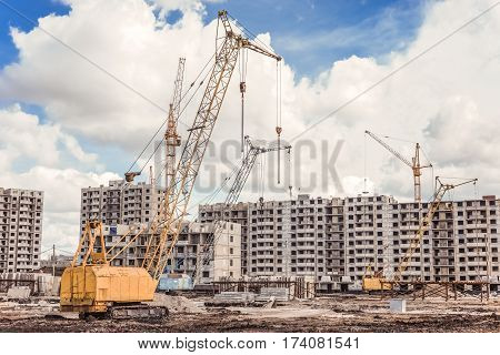 Construction area with the building machinery and incomplete skycrapers against a hard sky background.