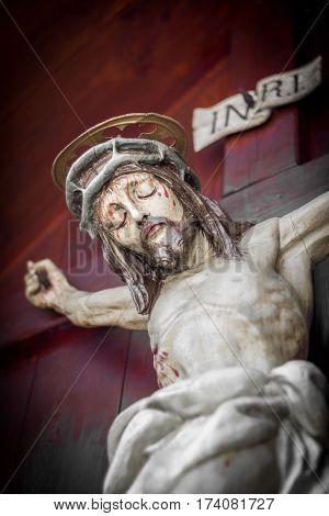 The bleeding body of Jesus Christ crucified on a wooden cross. Shallow depth of field.