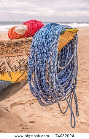 Close-up of a  blue and red mooring ropes tied around a stern of a yellow-blue colored wooden boat on the beach.