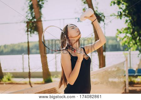 girl standing at the tennis nets and holding a tennis racket and bottle