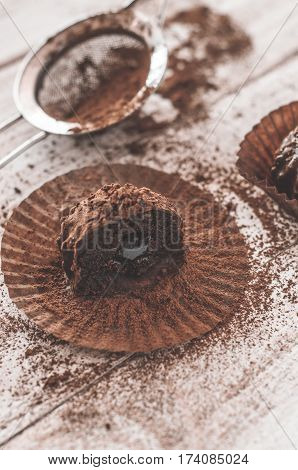 Chocolate chip muffin in brown wax paper. Unwrapped. Cocoa powder in the background.