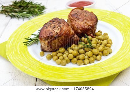 Juicy pork medallions wrapped in bacon serve with green peas and a sprig of rosemary on a plate on white wooden background. Close up