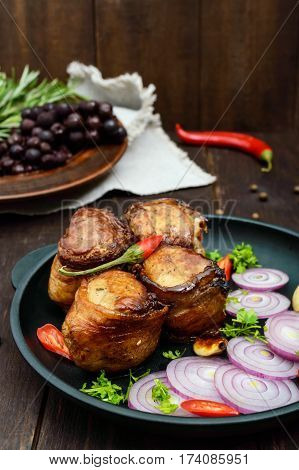 Juicy pork medallions wrapped in bacon serve on the iron pan on the dark wooden dackground.