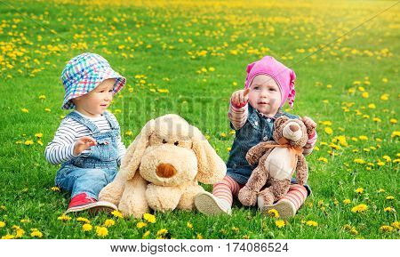 Little boy and girl in hats sitting on the field with soft toys in summer. Two cute one year old babies on the grass with dandelions