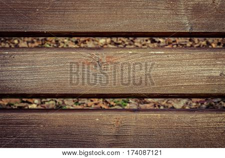 Brown wooden background. Planks with fuzzy grass and leaves in the background.