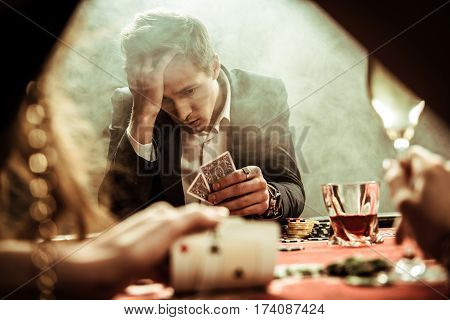 portrait of upset man looking at poker cards in hand