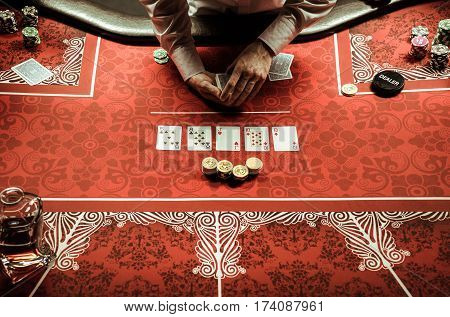 Partial view of croupier dealing card at poker table in casino