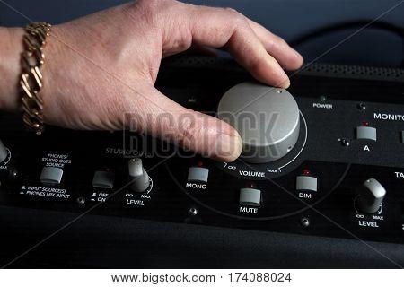 DJ hand pushing a volume knob on an amplifier closeup shot