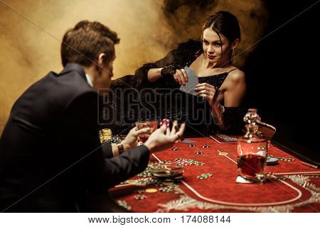 Elegant young woman lying on poker table and playing poker with man in suit