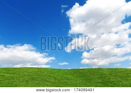 Landscape of grass field on bright sunny day. Nature beauty background, blue cloudy sky and summer green meadow. Outdoor lifestyle. Freedom concept.