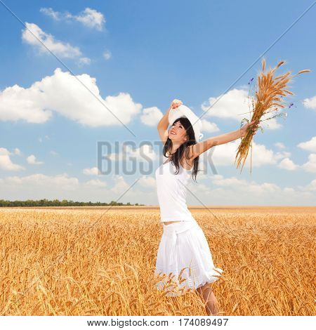Happy woman enjoying the life in the field with golden wheat. Nature beauty, blue cloudy sky and field of wheat. Outdoor lifestyle. Freedom concept. Woman in summer field