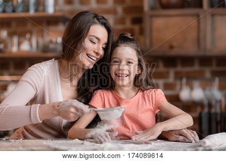 'Happy mother and daughter with flour on faces sifting flour at kitchen table