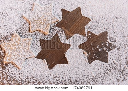 'Close-up top view of unbaked star shaped cookies in flour on table