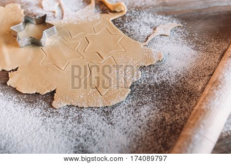 'Close-up view of unbaked cookies with cutter and rolling pin on table