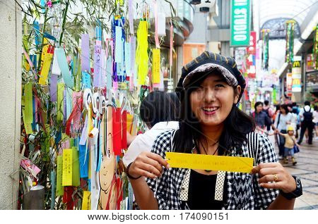 Traveller Thai Woman Join And Writing Her Wishes Small Pieces Of Paper And Hanging Them On Bamboo In