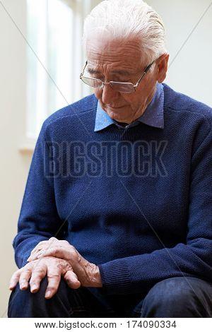 Senior Man Suffering With Parkinsons Diesease At Home
