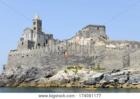 Portovenere Italy - 7 July 2015: Man rowing on his canoe in front of the old church on a rocky coastal outcrop at Portovenere Italy