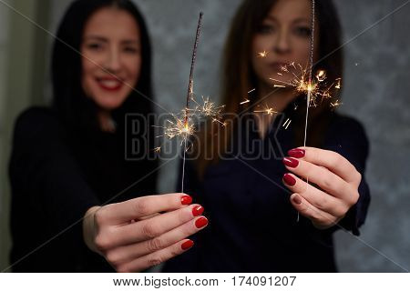 Beautiful women with red nails holding sparklers.
