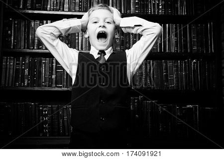 Smart boy in a suit stands in the library by the bookshelves and shouting. Educational concept. Science. Black-and-white portrait.