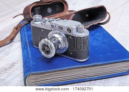 Vintage old film photo-camera in leather case and album.