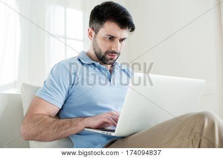 side view of concentrated man typing on laptop at home