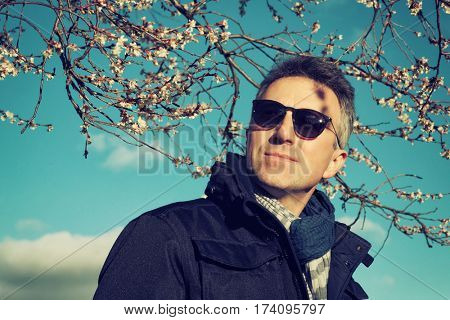 Handsome man. Outdoor spring male portrait. Attractive confident middle-aged man posing over blooming spring tree and blue sky.