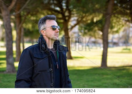 Handsome happy smiling man. Outdoor winter male portrait. Attractive confident middle-aged man in sunglasses walking in city park.
