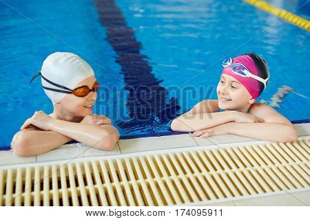 Cheerful boy and girl smiling and talking while taking a break after swimming holding onto pool border