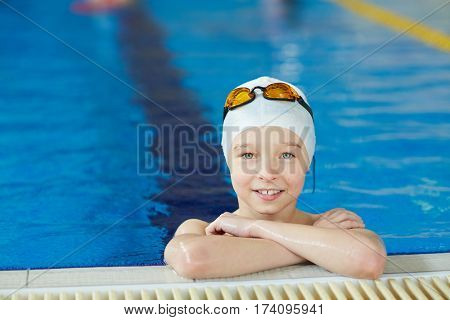 Portrait of cute energetic kid smiling to camera at border of pool during swimming lesson