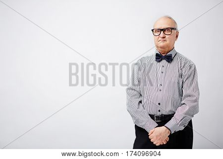 Elegant pensioner in glasses and striped shirt with bow tie standing with clasped hands and looking at camera with serious face expression