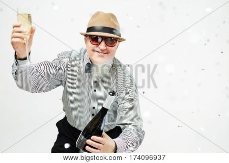 Portrait of stylish aged man in bowler hat and sunglasses celebrating birthday with champagne and confetti isolated on white background