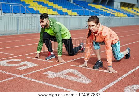 Couple of athletes, man and woman, standing close together on sprint tracks in stadium ready to start running competition