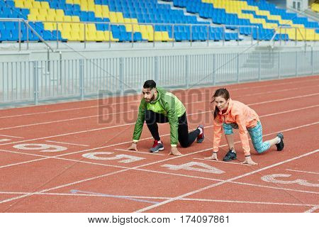 Wide shot of two young athletes, man and woman, prepairing for running competition waiting for signal on start positions in empty stadium