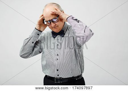 Portrait of upset senior man in striped shirt with bow tie holding his head, looking down and thinking hard
