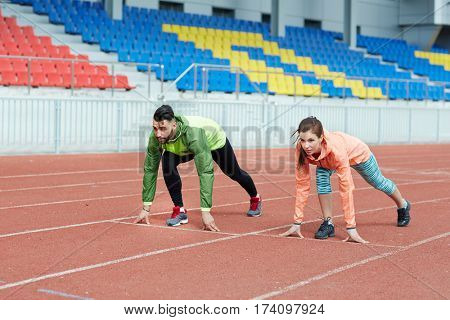 Determined athletes, man and woman, starting race on running track in empty stadium