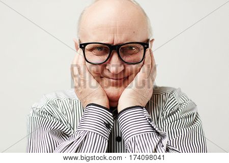 Portrait of charming aged man in eyeglasses and striped shirt making funny face by squishing cheeks with his hands
