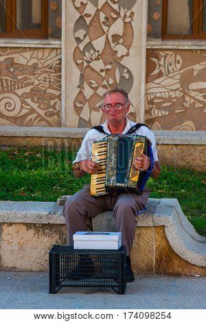 CONSTANTA ROMANIA - AUGUST 21 2010 street musician plays the accordion