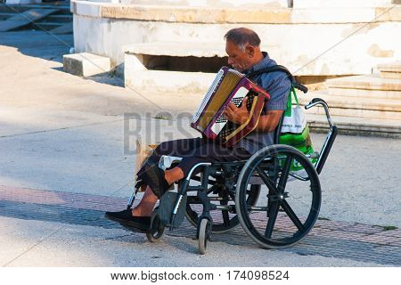 CONSTANTA ROMANIA - AUGUST 21 2010. street musician in a wheelchair playing the accordion