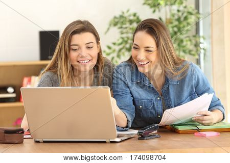 Two students studying together on line with a laptop in the living room at home with a homey background