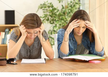 Front view of a concentrated students studying together sitting in a table in the living room at home
