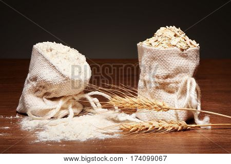Burlap Bags Of Flour And Oatmeal, Wheat Ears On Table